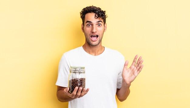 Spaanse knappe man die zich gelukkig en verbaasd voelt over iets ongelooflijks. koffiebonen fles