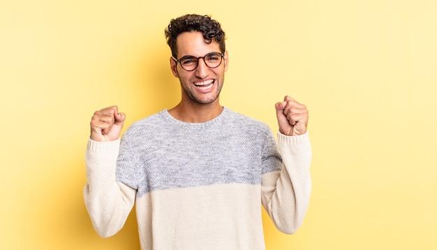 Spaanse knappe man die zich gelukkig, positief en succesvol voelt en de overwinning viert