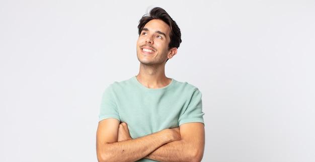 Spaanse knappe man die zich gelukkig, trots en hoopvol voelt, zich afvraagt of denkt, opkijkt om ruimte te kopiëren met gekruiste armen