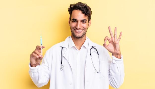 Spaanse knappe man die zich gelukkig voelt, goedkeuring toont met een goed gebaar arts en srynge-concept