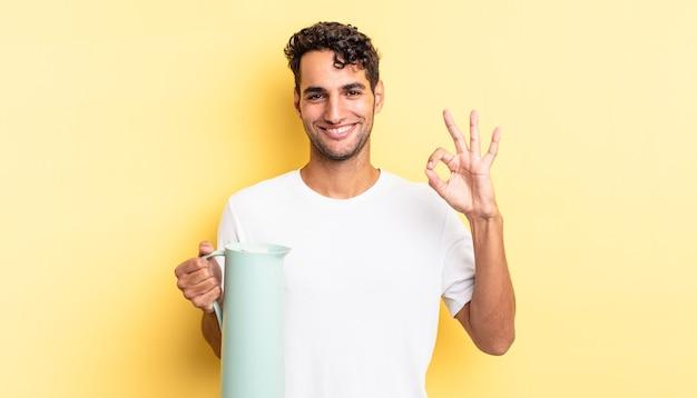 Spaanse knappe man die zich gelukkig voelt, goedkeuring toont met een goed gebaar. koffie thermos concept