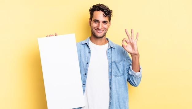 Spaanse knappe man die zich gelukkig voelt, goedkeuring toont met een goed gebaar. leeg canvasconcept
