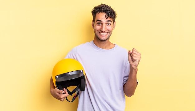 Spaanse knappe man die zich geschokt voelt, lacht en succes viert. motorhelm concept
