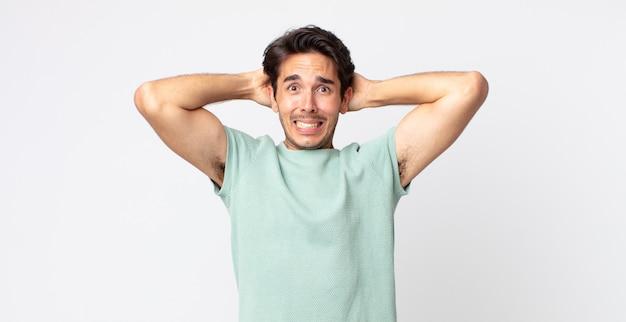 Spaanse knappe man die zich gestrest, bezorgd, angstig of bang voelt, met de handen op het hoofd, in paniek bij vergissing