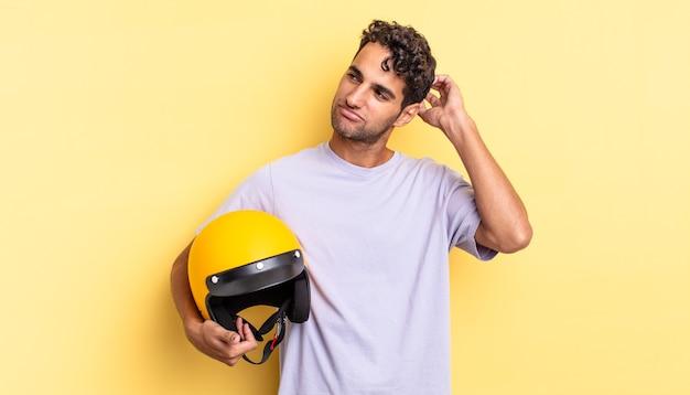 Spaanse knappe man die zich verbaasd en verward voelt, hoofd krabben. motorhelm concept