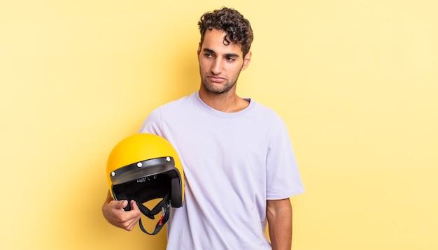Spaanse knappe man die zich verdrietig, overstuur of boos voelt en opzij kijkt. motorhelm concept