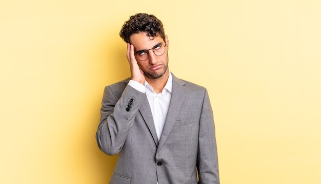 Spaanse knappe man die zich verveeld, gefrustreerd en slaperig voelt na een vermoeiende bedrijfsconcept