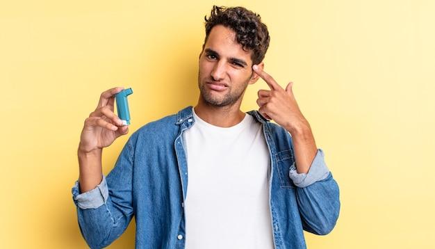 Spaanse knappe man die zich verward en verbaasd voelt en laat zien dat je gek bent. astma concept