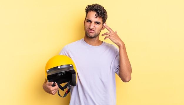 Spaanse knappe man die zich verward en verbaasd voelt en laat zien dat je gek bent. motorhelm concept