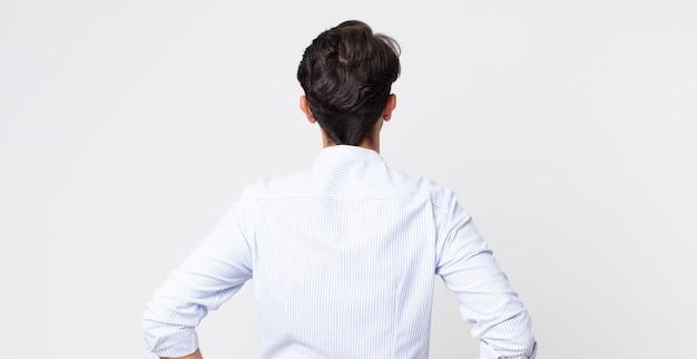 Spaanse knappe man die zich verward of vol voelt of twijfels en vragen, zich afvragend, met de handen op de heupen, achteraanzicht