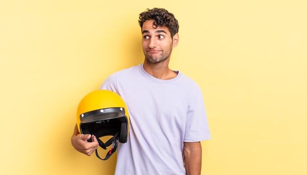 Spaanse knappe man die zijn schouders ophaalt, zich verward en onzeker voelt. motorhelm concept