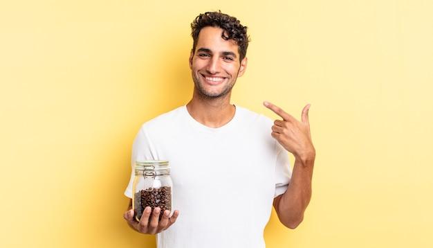 Spaanse knappe man glimlachend vol vertrouwen wijzend naar eigen brede glimlach. koffiebonen fles
