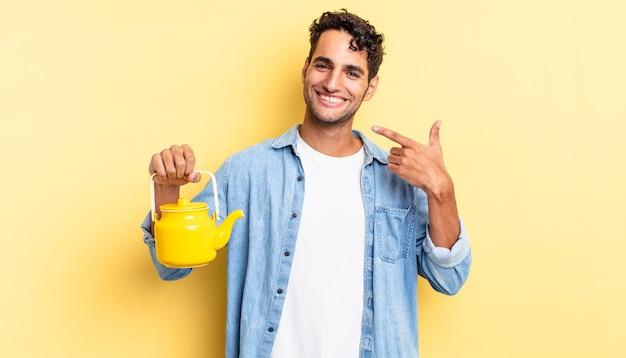 Spaanse knappe man glimlachend vol vertrouwen wijzend naar eigen brede glimlach. theepot concept