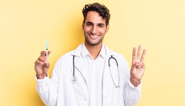 Spaanse knappe man glimlacht en ziet er vriendelijk uit, met nummer drie arts en srynge-concept