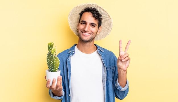 Spaanse knappe man glimlacht en ziet er vriendelijk uit, met nummer twee boer en cactusconcept