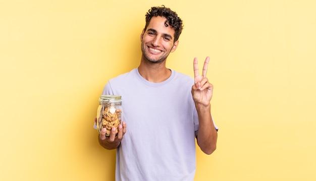 Spaanse knappe man lacht en ziet er gelukkig uit, gebarend overwinning of vrede. koekjes concept