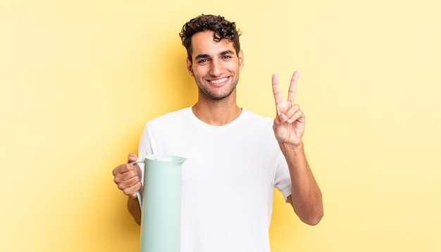 Spaanse knappe man lacht en ziet er gelukkig uit, gebarend overwinning of vrede. koffie thermos concept