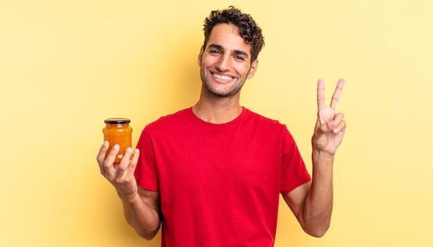 Spaanse knappe man lacht en ziet er gelukkig uit, gebarend overwinning of vrede. perzik jam