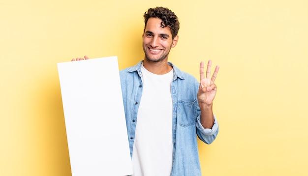 Spaanse knappe man lacht en ziet er vriendelijk uit, met nummer drie. leeg canvasconcept