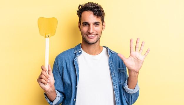 Spaanse knappe man lacht en ziet er vriendelijk uit, met nummer vijf. doodt vliegen concept