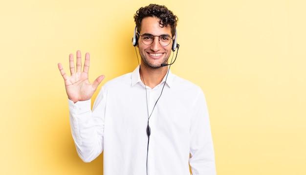 Spaanse knappe man lacht en ziet er vriendelijk uit, met nummer vijf. telemarketeer concept