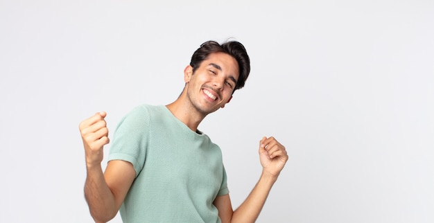 Spaanse knappe man lacht, voelt zich zorgeloos, ontspannen en gelukkig, danst en luistert naar muziek, plezier op een feestje