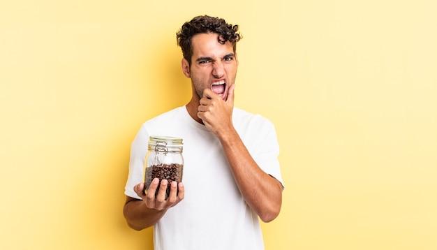 Spaanse knappe man met mond en ogen wijd open en hand op kin. koffiebonen fles