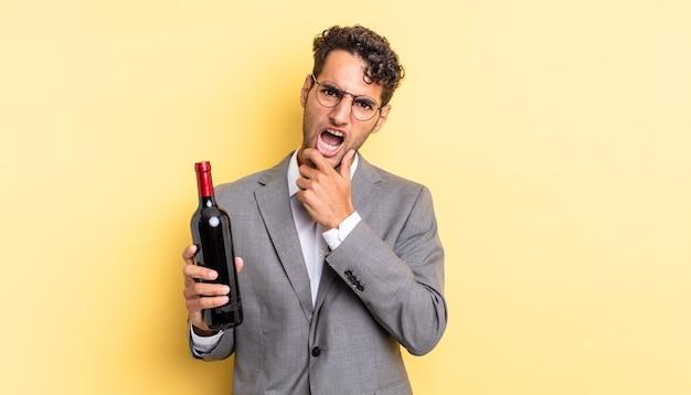Spaanse knappe man met mond en ogen wijd open en hand op kin. wijnfles concept