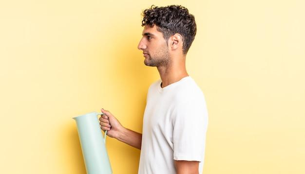 Spaanse knappe man op profielweergave denken, verbeelden of dagdromen. koffie thermos concept