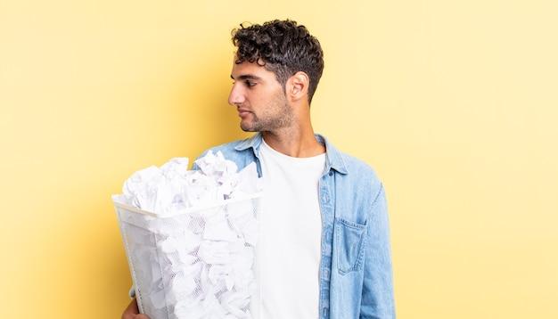 Spaanse knappe man op profielweergave denken, verbeelden of dagdromen. papier ballen prullenbak concept