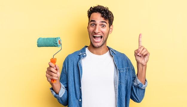 Spaanse knappe man voelt zich een gelukkig en opgewonden genie nadat hij een idee heeft gerealiseerd. roller verf concept