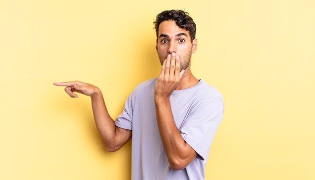 Spaanse knappe man voelt zich gelukkig, bedekt de mond met de hand en wijst naar de laterale kopieerruimte