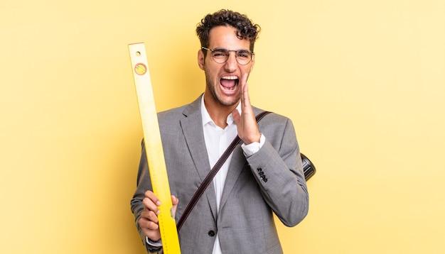 Spaanse knappe man voelt zich gelukkig en geeft een grote schreeuw met de handen naast de mond. architect concept