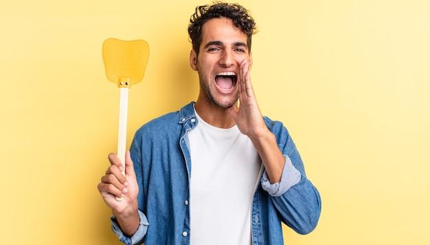 Spaanse knappe man voelt zich gelukkig en geeft een grote schreeuw met de handen naast de mond. doodt vliegen concept