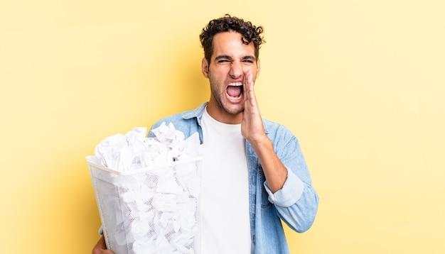 Spaanse knappe man voelt zich gelukkig en geeft een grote schreeuw met de handen naast de mond. papier ballen prullenbak concept