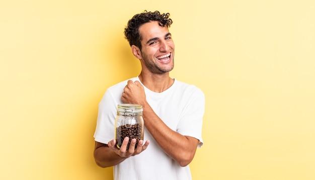 Spaanse knappe man voelt zich gelukkig en staat voor een uitdaging of feest. koffiebonen fles