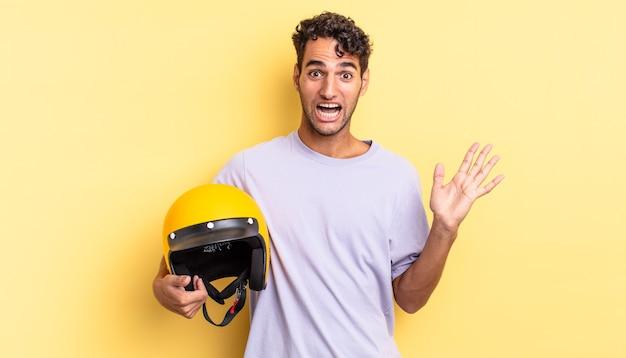 Spaanse knappe man voelt zich gelukkig en verbaasd over iets ongelooflijks. motorhelm concept