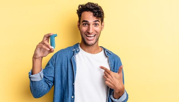 Spaanse knappe man voelt zich gelukkig en wijst naar zichzelf met een opgewonden astma concept