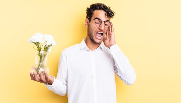 Spaanse knappe man voelt zich gelukkig, opgewonden en verrast. bloemen pot concept