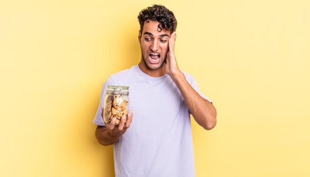 Spaanse knappe man voelt zich gelukkig, opgewonden en verrast. koekjes concept