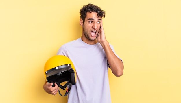Spaanse knappe man voelt zich gelukkig, opgewonden en verrast. motorhelm concept