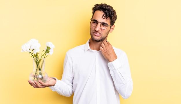 Spaanse knappe man voelt zich gestrest, angstig, moe en gefrustreerd. bloemen pot concept