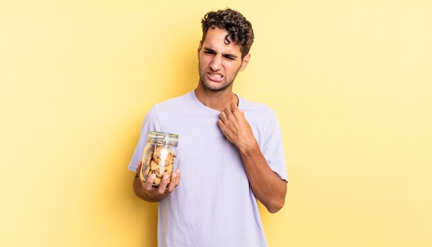 Spaanse knappe man voelt zich gestrest, angstig, moe en gefrustreerd. koekjes concept