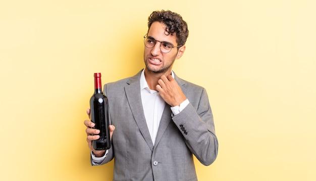 Spaanse knappe man voelt zich gestrest, angstig, moe en gefrustreerd. wijnfles concept