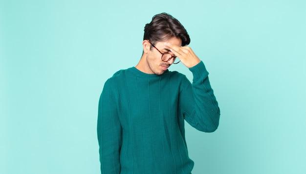 Spaanse knappe man voelt zich gestrest, ongelukkig en gefrustreerd, raakt het voorhoofd aan en lijdt aan migraine of ernstige hoofdpijn