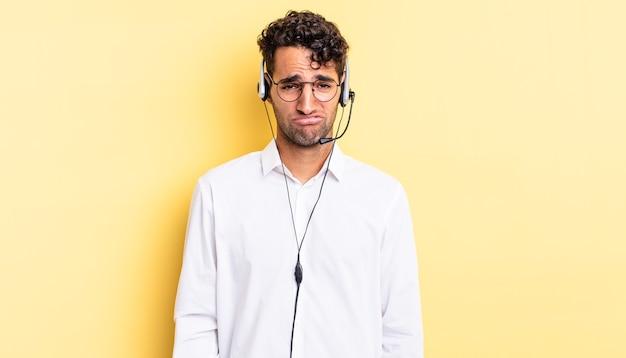 Spaanse knappe man voelt zich verdrietig en zeurt met een ongelukkige blik en huilt. telemarketeer concept