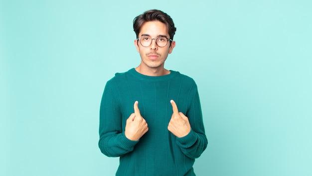 Spaanse knappe man wijst naar zichzelf met een verwarde en vragende blik, geschokt en verrast om gekozen te worden