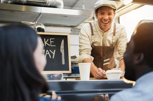 Spaanse man die afhaalmaaltijden serveert in een foodtruck - focus op het gezicht van de chef