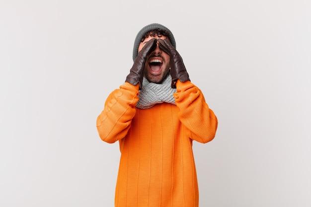 Spaanse man die zich gelukkig, opgewonden en positief voelt, een grote schreeuw geeft met de handen naast de mond, roept