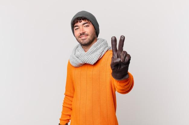 Spaanse man lacht en ziet er gelukkig, zorgeloos en positief uit, gebaart overwinning of vrede met één hand